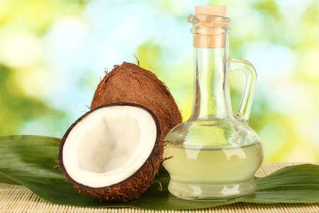 noix de coco: carafe avec de l'huile de noix de coco et de noix de coco sur fond vert