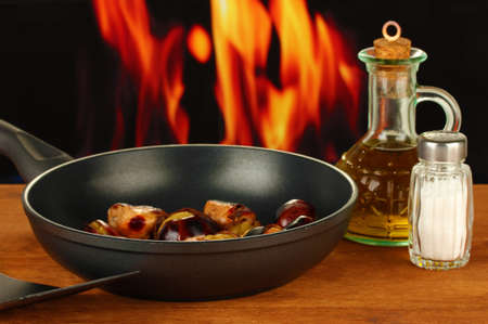 buckeye seed: roasted chestnuts in the pan and decanter with oil, salt and pepper on wooden table close-up