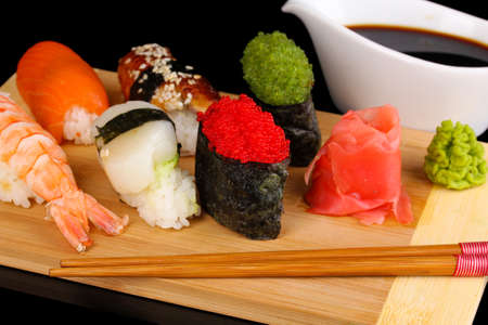 delicious sushi served on wooden board close-up photo