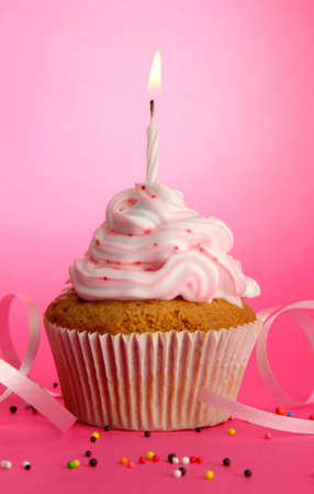 tasty birthday cupcake with candle, on pink background photo