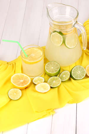 Citrus lemonade in glass and pitcher of citrus around on yellow fabric on white wooden table close-up Stock Photo - 15627637
