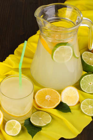 Citrus lemonade in glass and pitcher of citrus around on yellow fabric on wooden table close-up Stock Photo - 15627775