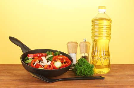 dripping pan: frying pan with vegetables on yellow background Stock Photo