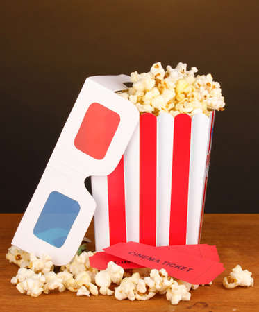 popcorn with tickets and cinema glasses on wooden table on brown background photo