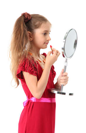 little girl in her mother's dress, is trying painting her lips, isolated on white Stock Photo - 15736417