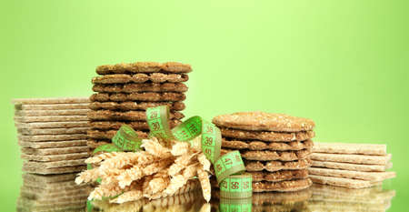 tasty crispbread, ears and measuring tape, on green background Stock Photo - 15664900