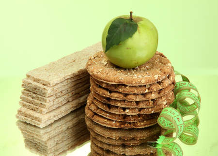tasty crispbread, apple and measuring tape, on green background Stock Photo - 15665093
