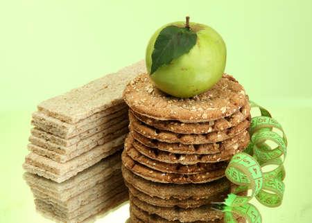 tasty crispbread, apple and measuring tape, on green background Stock Photo - 15665093