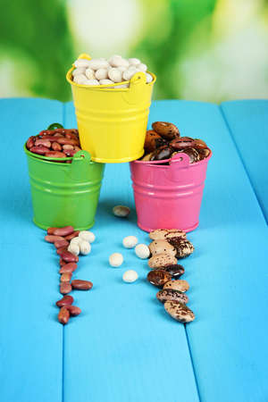 Different types of beans in colored buckets on blue wooden table on natural background Stock Photo - 15665397