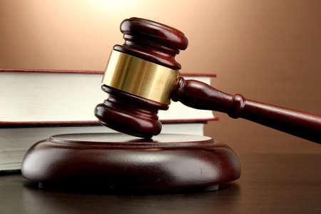 derecho penal: Mazo de madera y libros sobre la mesa de madera, sobre fondo marr�n