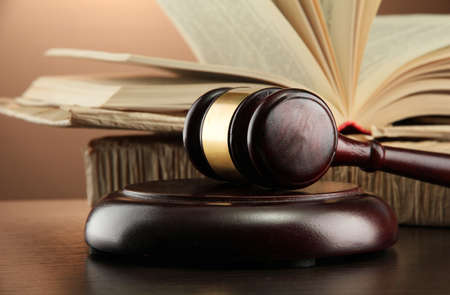 legal court: wooden gavel and books on wooden table,on brown background