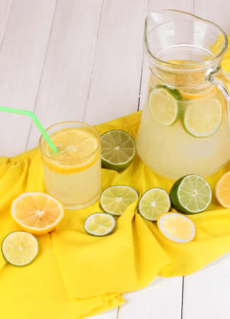 Citrus lemonade in glass and pitcher of citrus around on yellow fabric on white wooden table close-up Stock Photo - 15665108