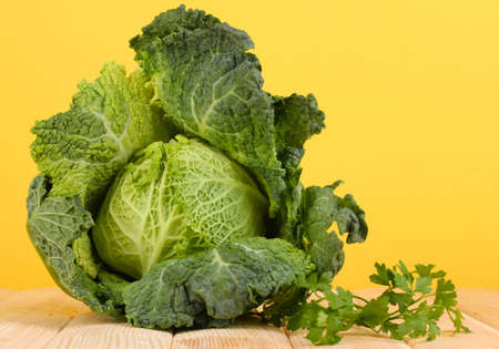 Fresh savoy cabbage on wooden table on yellow background photo
