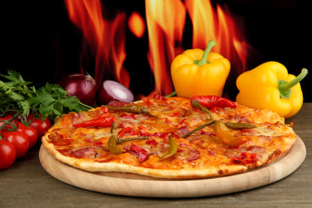 Tasty pepperoni pizza with vegetables on wooden board on flame background Stock Photo - 15684334