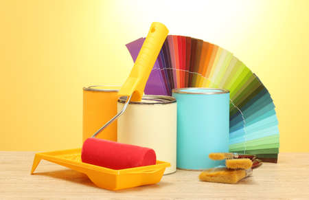 tin cans with paint, roller, brushes and bright palette of colors on wooden table on yellow background Stock Photo - 15718082