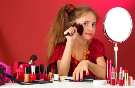 little girl in her mothers dress with make up brushes photo