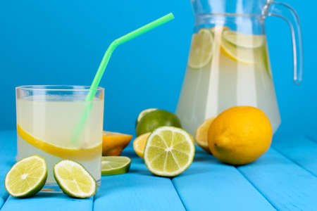 Citrus lemonade in pitcher and glass of citrus around on wooden table on blue background Stock Photo - 15718241