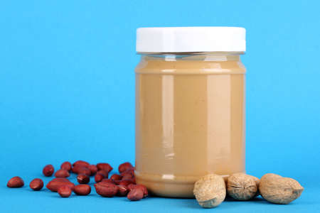 Delicious peanut butter in jar of peanut near on blue background Stock Photo - 15718362