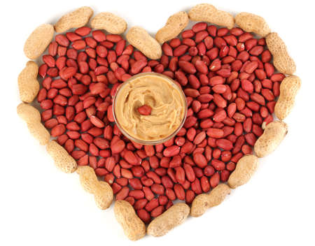 Delicious peanut butter in glass plate on picture of peanuts in form of heart isolated on white close-up Stock Photo - 15718468