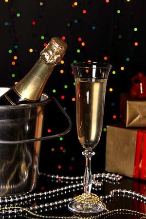 bouteille champagne: Champagne de f�te avec verre de vin sur fond de lumi�res de No�l