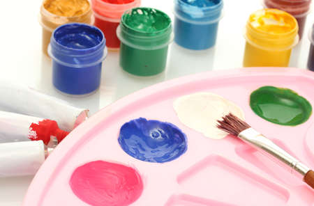 Tubes with colorful watercolors and jars with gouache and palette on white background close-up photo