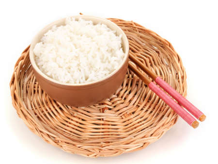 Bowl of rice and chopsticks on wicker mat isoalted on white photo