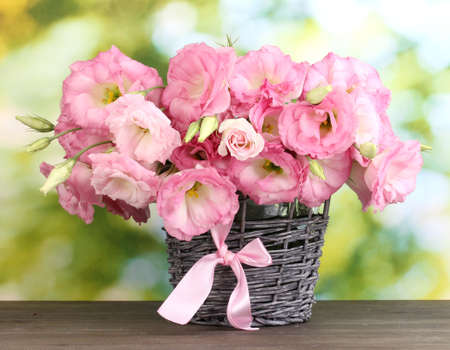 bouquet of eustoma flowers in  wicker vase, on wooden table, on green background 스톡 콘텐츠