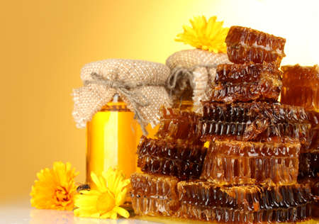 sweet honeycombs,jar with honey and flowers, on yellow background photo