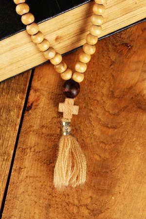 the Wooden rosary beads and holy bible on wooden background close-up photo