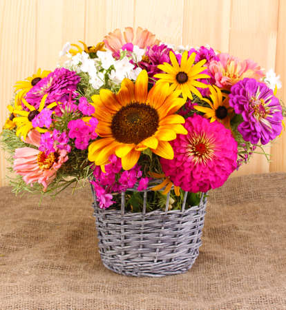 Beautiful bouquet of bright flowers on sacking on wooden background photo