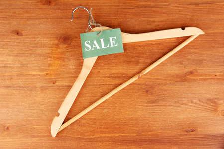 paper hanger: coat hanger with sale tag on wooden background