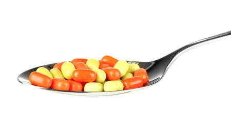 colorful pills on spoon on white background close-up Stock Photo - 15736445