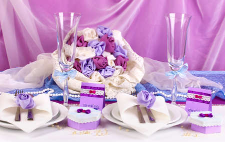 a frill: Serving fabulous wedding table in purple color on white and purple fabric background Stock Photo