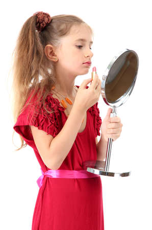 little girl in her mothers dress, is trying painting her lips, isolated on white photo
