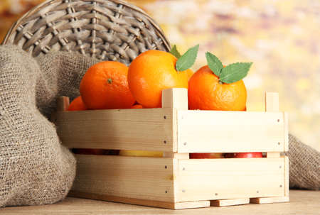 Ripe tasty tangerines with leaves in wooden box on table on orange background Stock Photo - 15739113