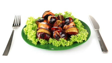 buckeye seed: roasted chestnuts with lettuce in the green plate with fork and knife isolated on white Stock Photo