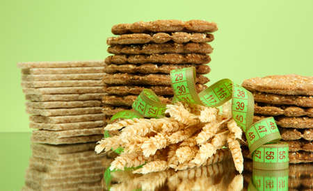 tasty crispbread, ears and measuring tape, on green background photo