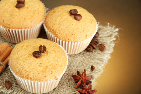 tasty muffin cakes on burlap, spices and coffee seeds, on brown background photo