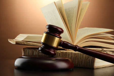 legal books: wooden gavel and books on wooden table,on brown background