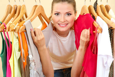 choose person: beautiful young woman near rack with hangers Stock Photo
