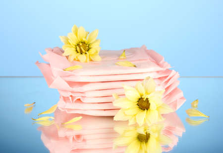 Panty liners in individual packing and yellow flowers on blue background close-up Stock Photo - 15738363
