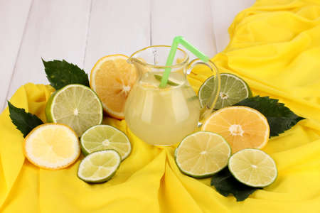 Citrus lemonade in glass pitcher of citrus around on yellow fabric on white wooden table close-up Stock Photo - 15757800