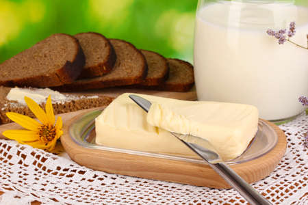 Butter on wooden holder surrounded by bread and milk on natural background close-up Stock Photo - 15758248