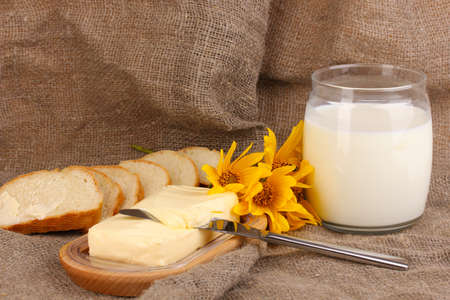 Butter on wooden holder surrounded by bread and milk on sacking background photo