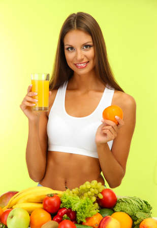 beautiful young woman with fruits and vegetables and glass of juice, on green background Stock Photo - 15958794