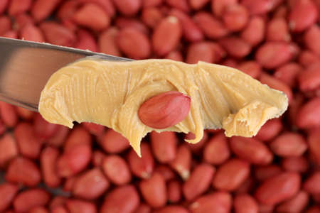 Delicious peanut butter on knife on peanuts background close-up Stock Photo - 15835778