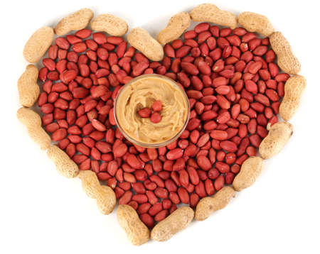 Delicious peanut butter in glass plate on picture of peanuts in form of heart isolated on white close-up Stock Photo - 15835420