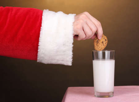 hots: Santa Claus hand holding chocolate cookie on brown background