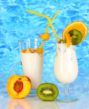 Delicious milk shakes with fruit on table on blue sea background photo
