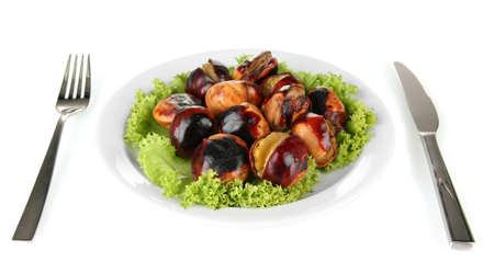 buckeye seed: roasted chestnuts with lettuce in the white plate with fork and knife isolated on white Stock Photo